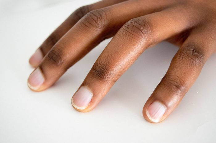 African American Dark brown skin Woman hand with french manicure isolated on white background. Close-up. Untouched.