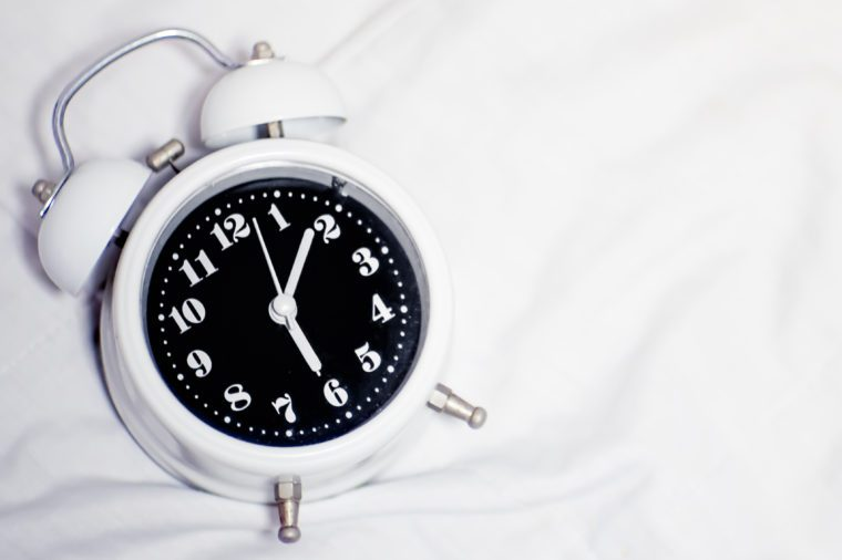 Alarm ring bells clock on white fabric blanket or bedspread background on bed, time around 6 o'clock