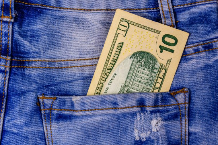 American ten dollar banknotes in pocket of blue jeans