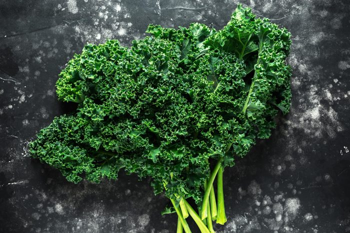 Raw organic freshly picked green curly kale on black table