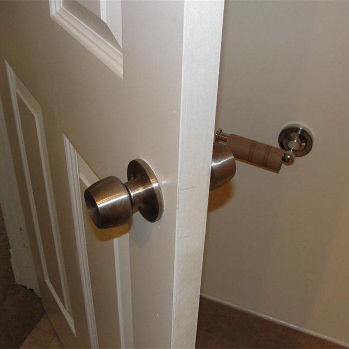 toilet paper holder behind door