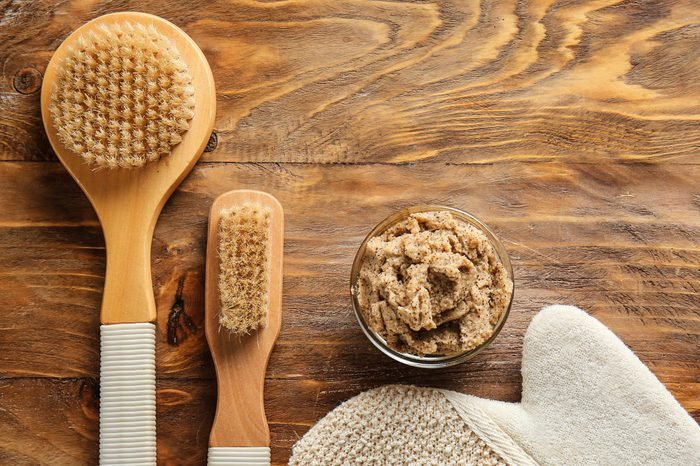 Brushes and body scrub on wooden background
