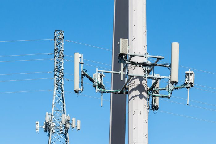 Cell tower antennas mounted on steel power poles close up. Lattice structure tower in blurred background. Blue sky.