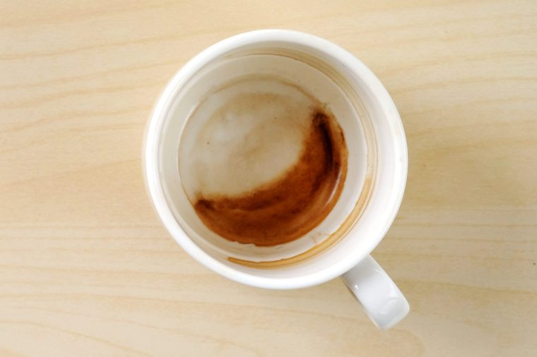 Coffee stain in cup on wood background, with copy space