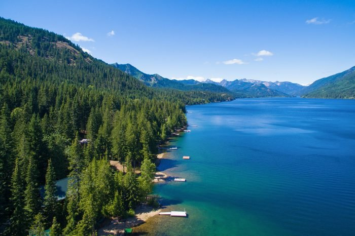 Cold blue mountain lake in state Washington, Lake Cle Elum in the middle of the summer with waterfront properties, mountains and green fir trees. Aerial photo.