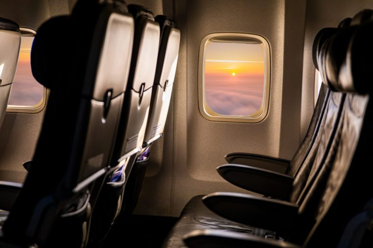 Empty airplane seats in the cabin in sunset light .