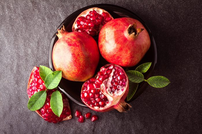 Fresh red pomegranate and seed with leaves over black stone background , overhead or top view