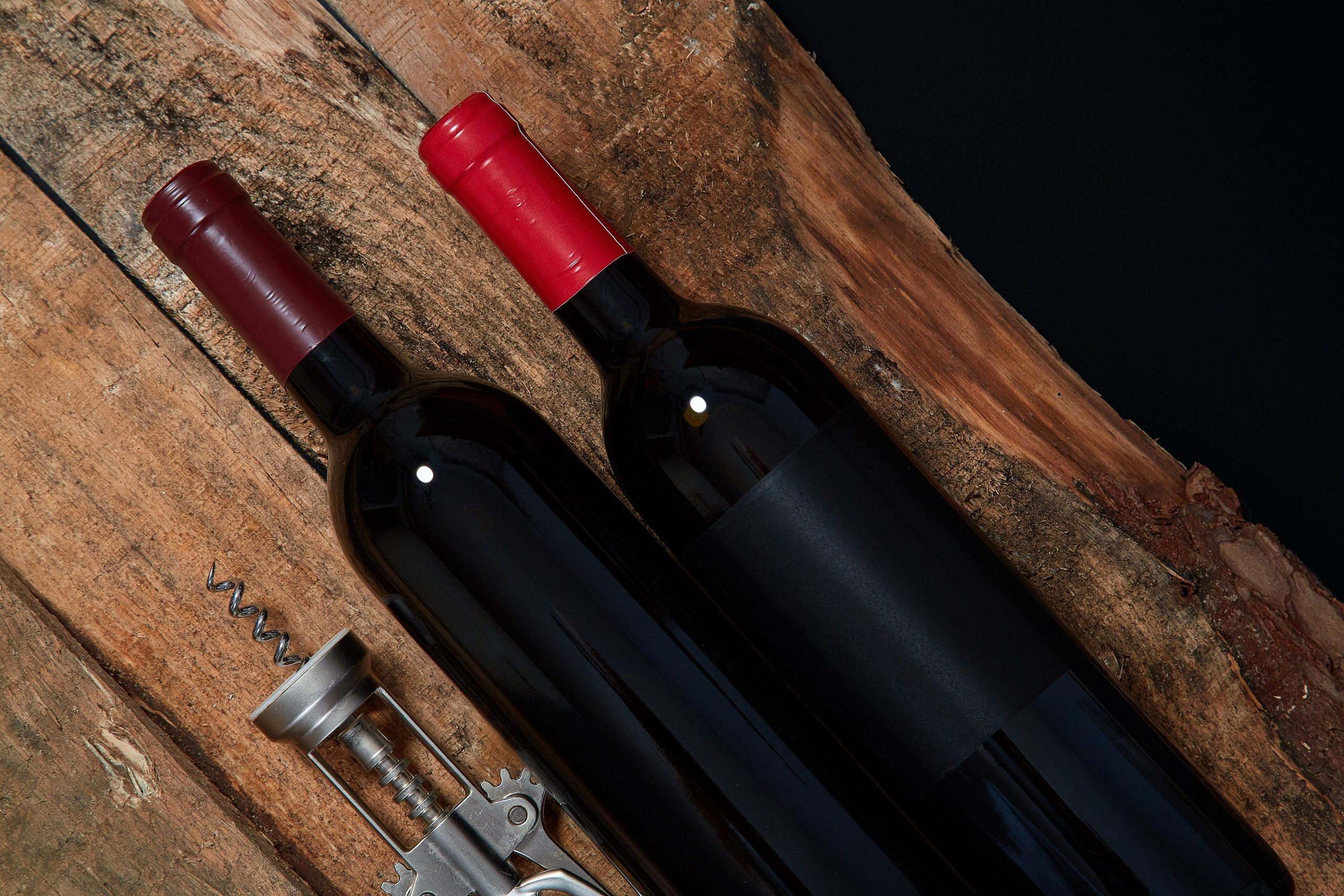 From above of arranged corkscrew and few bottle of red wine on wood above black background
