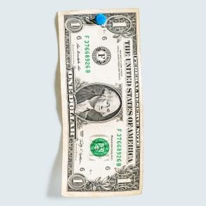 one dollar bill pinned with a blue thumbtack