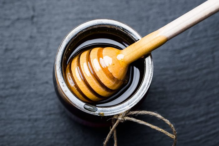 Glass jar of honey and wooden dipper in honey on black background