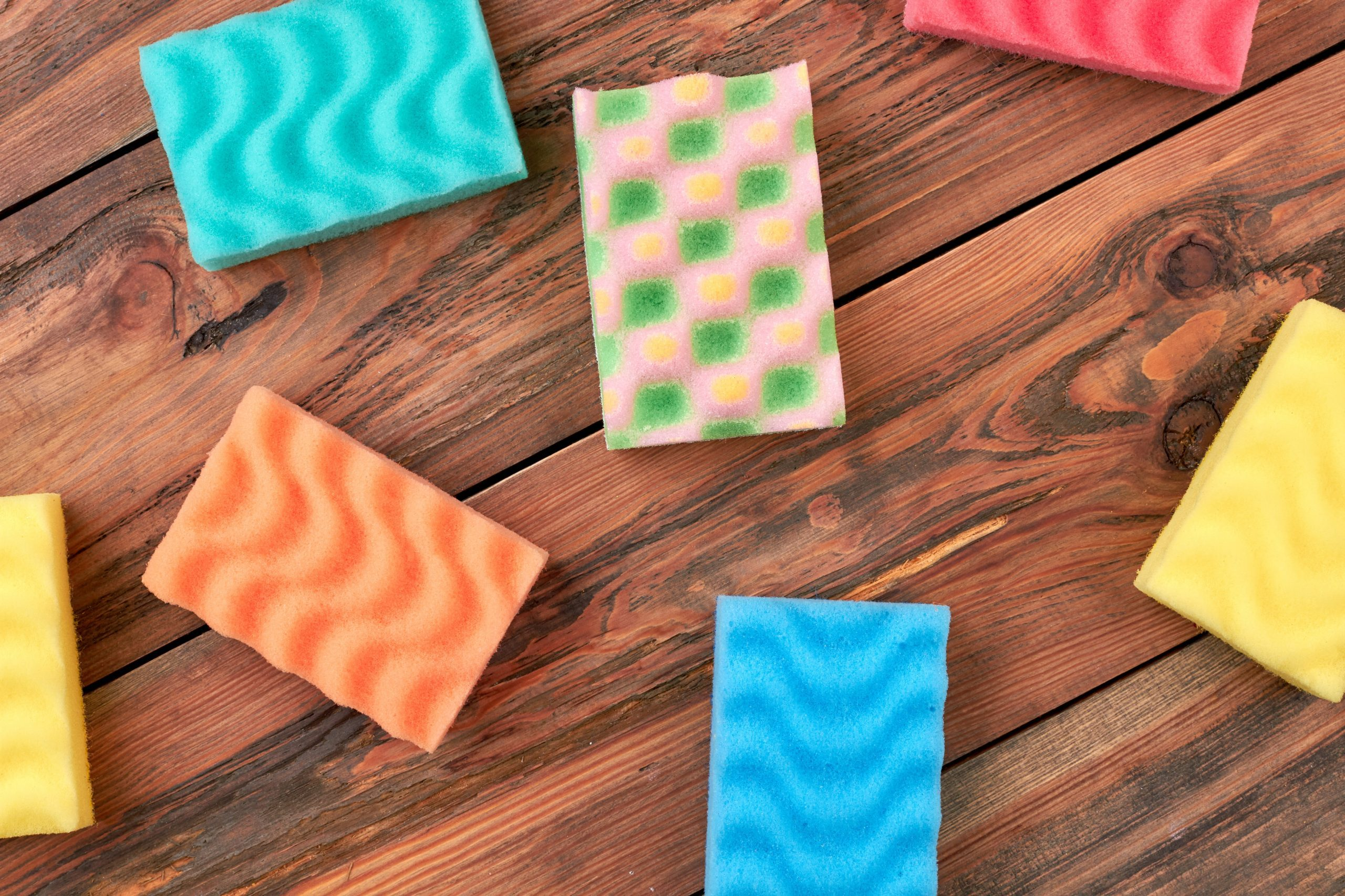 Group of multicolored kitchen sponges. Set of colorful sponges for kitchen on wooden background. Housekeeping and cleaning concept.