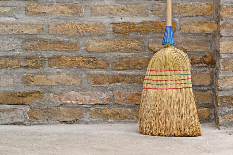 Household Used Broom For Floor Dust Cleaning Leaning on Brick Wall