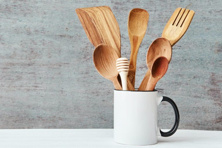 Kitchen utensils in ceramic cup on gray background, copy space