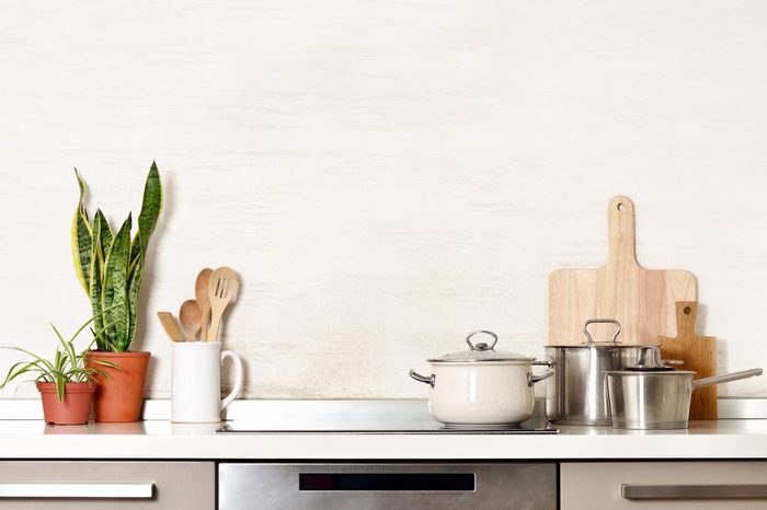 Kitchen utensils on a modern home kitchen table top, front view background with blank space for a text