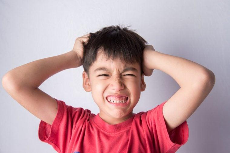 Little boy itchy his head stress face headache