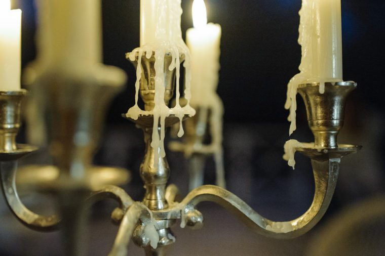 Metal candlestick with burning candles and melting wax