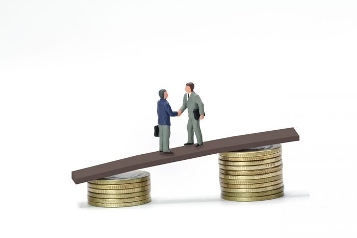 Miniature people, two businessmen shaking hand on the bridge between stack of coins, business concept