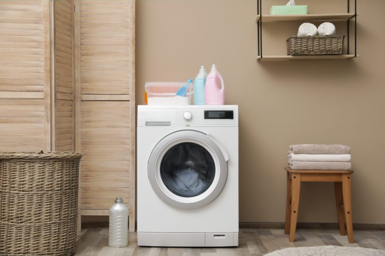 Modern washing machine near color wall in laundry room interior