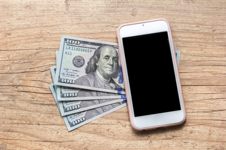 Money from USA. Dollars. North american currency. Blank smartphone screen and cash bills on wooden table.