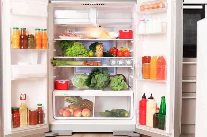 Open refrigerator filled with different food in kitchen