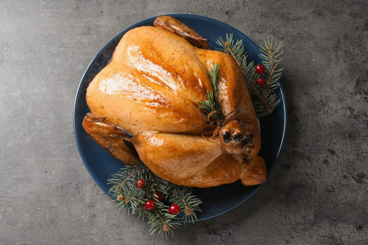 Platter of cooked turkey with cranberry and fir tree branches on grey background, top view