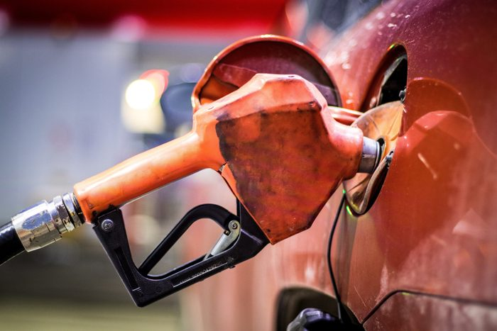 Red gas pump nozzle resting within the opened tank of a vehicle