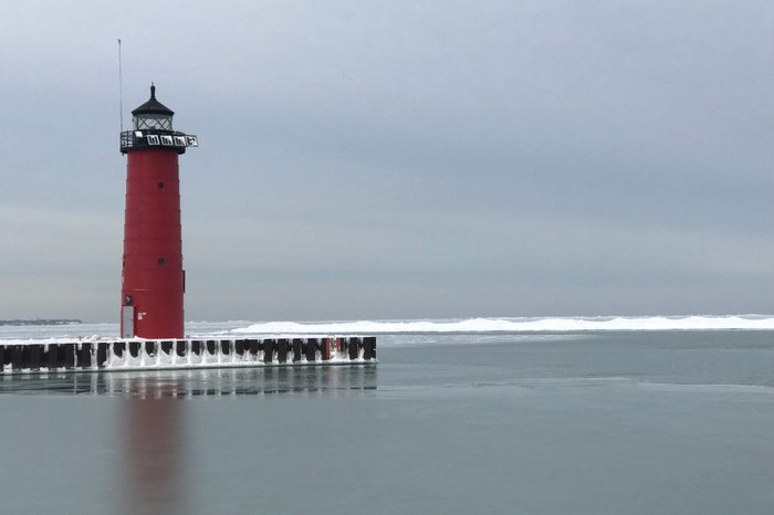Red lighthouse on blue cloud sky in winter at Michigan Lake in Kenosha, Wisconsin, USA.