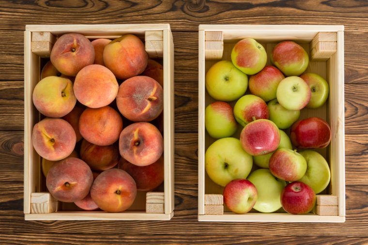 Small wooden crates of healthy fresh fruit filled with ripe peaches and variegated apples view from above on a table at farmers market