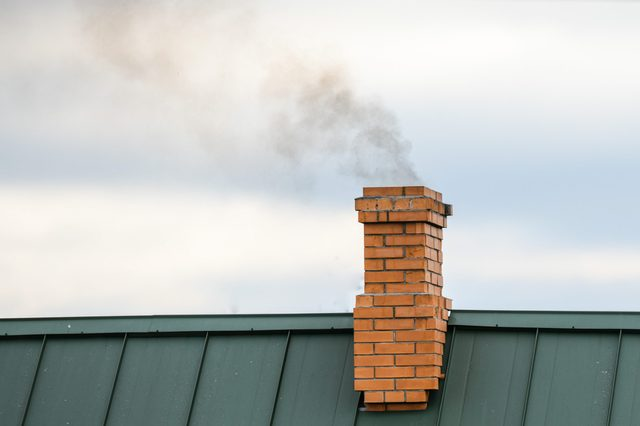 Smoke from the chimney, heating. smoke billowing. coming out of a house chimney against a blue sky background