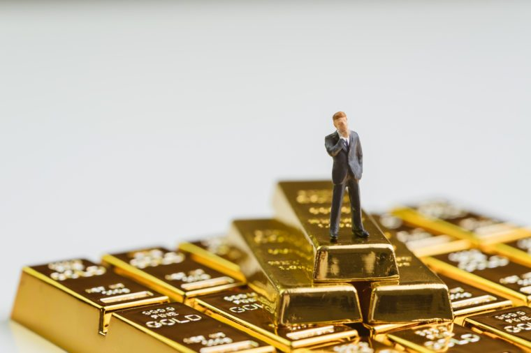 Success miniature rich businessman standing on stack of gold bar, bullion or ingot using as wealth management, gold investment and financial asset.