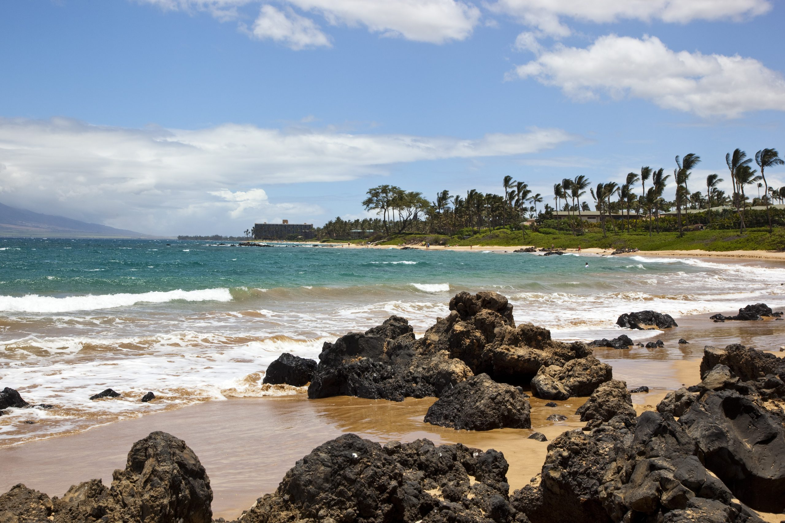 Surf crashing against rocks on a beach in Wailea, Maui, Hawaii