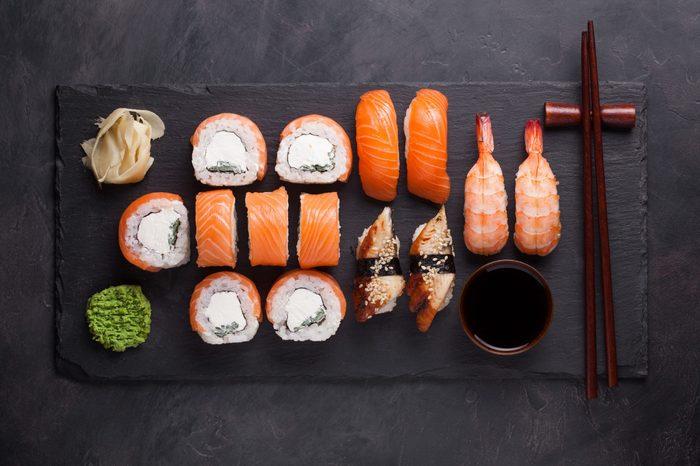 Sushi Set sashimi with salmon, shrimp, eel and sushi rolls philadelphia served on stone slate. Top view.