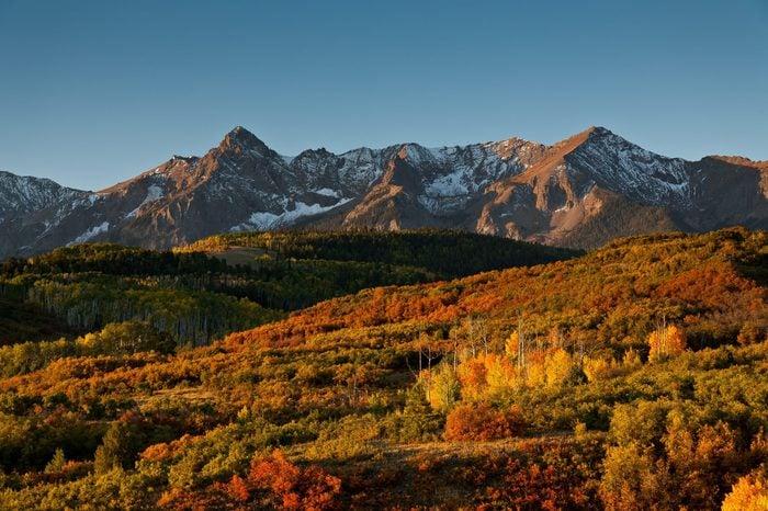 The rising sun illuminates Sneffles Range at Dallas Divide in Colorado's San Juan Mountains