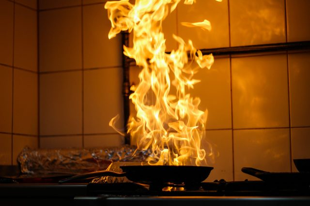 The chef cooking and makes a fire in a pan. Cooking with fire. Crown food.Flame on kitchen