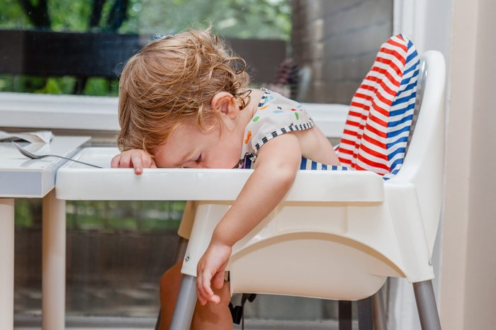 Tired child sleeping in highchair after the lunch. Baby over eating and fall asleep just after feeding, lying his face on the table tray.