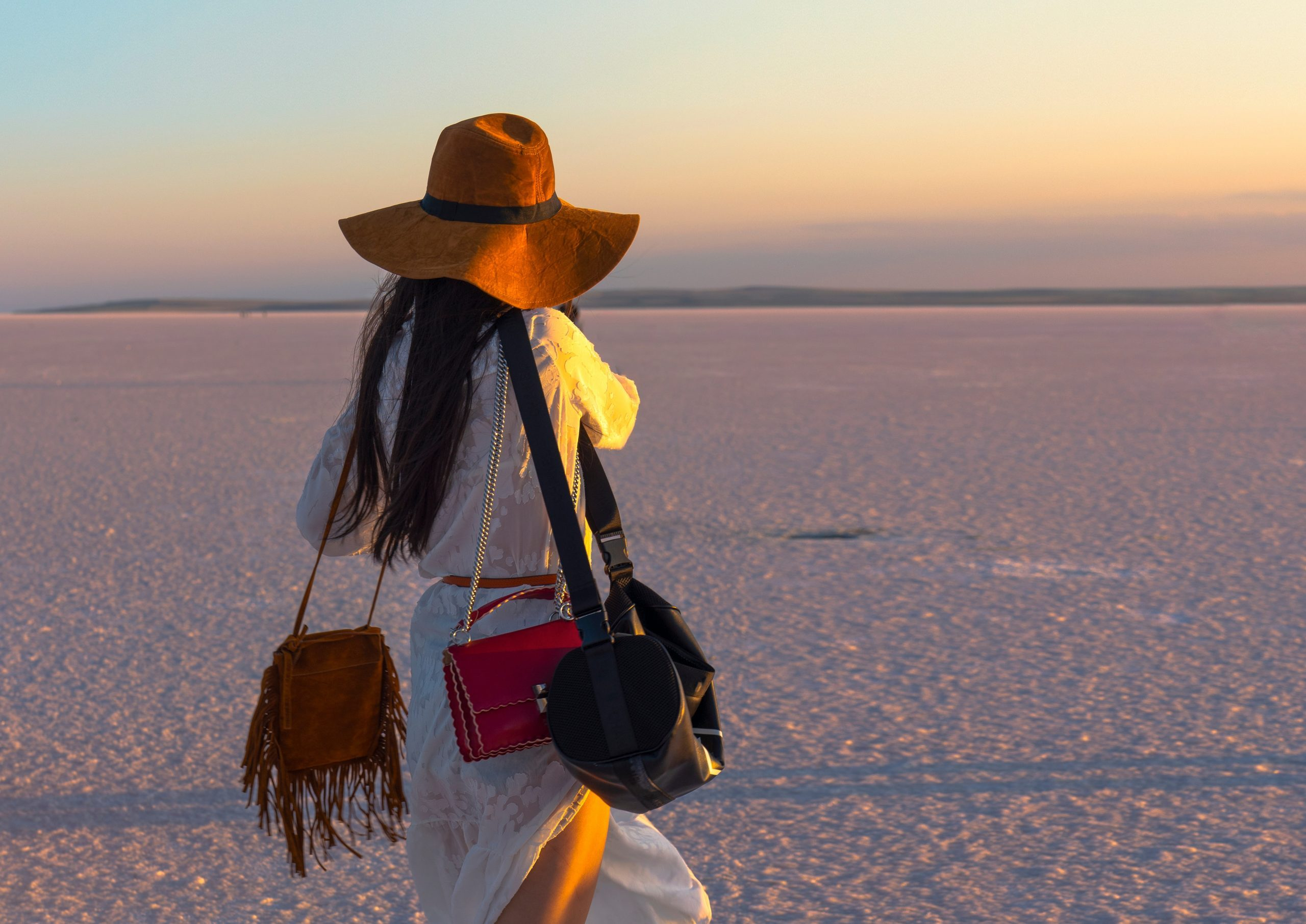 Tourist woman with many colorful purses in salt lake. Fashion and tourism addicted. Love for shopping.