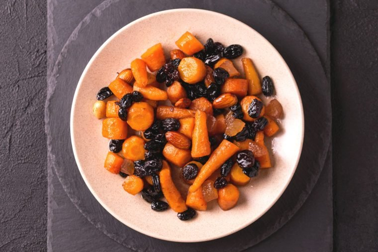 Traditional Jewish Tzimmes dessert with carrot, raisins and dried fruits on table. Top view. Israeli cuisine