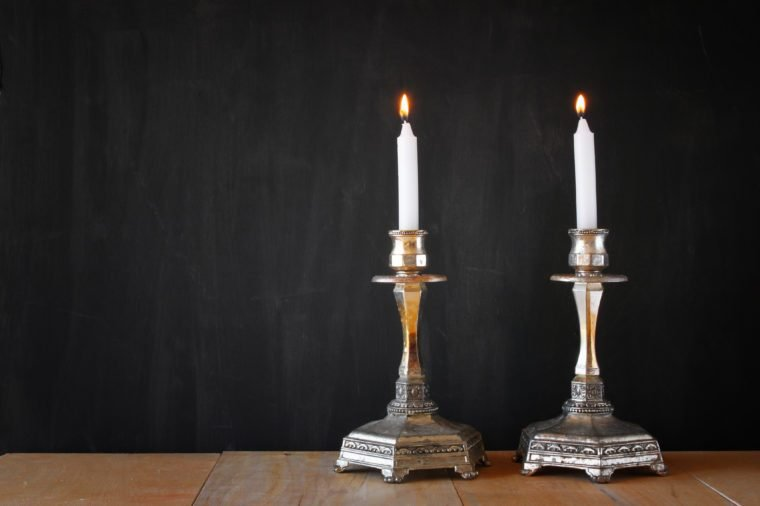 Two candlesticks with burning candles over wooden table and blackboard background