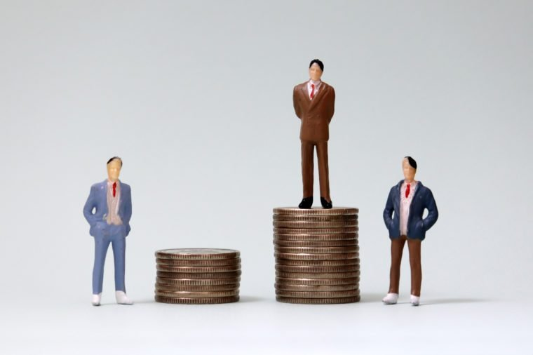 Two miniature men standing next to a miniature man standing on a pile of coins.