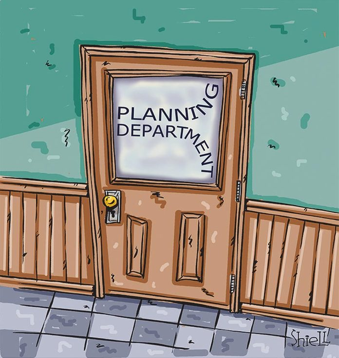 "door with a glass panel that reads ""planning department"" written as if the writer ran out of room for all the letters"
