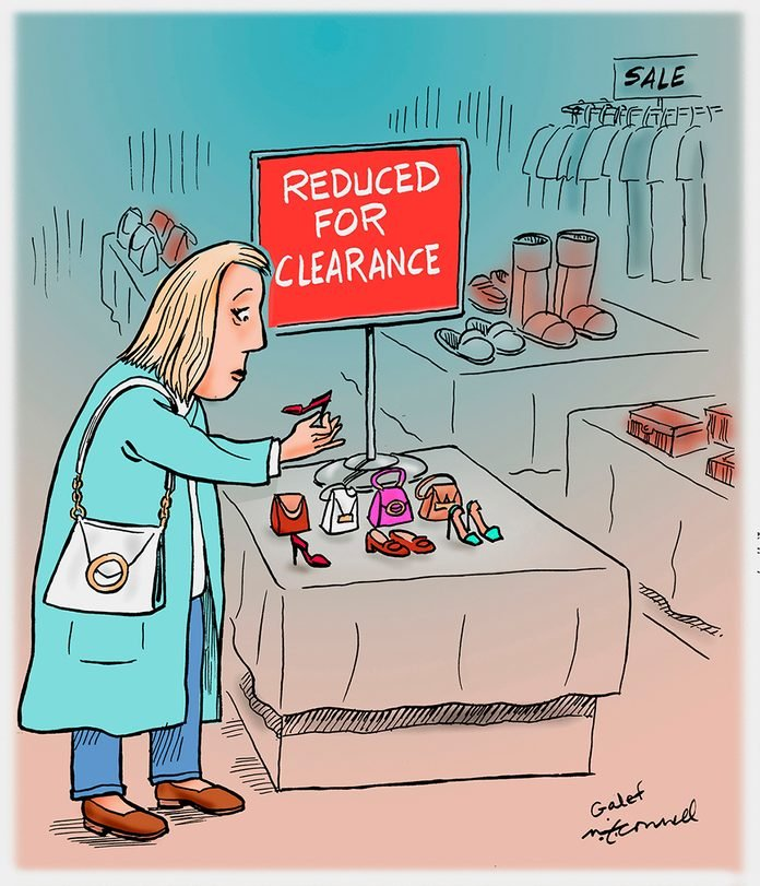 "in a store, a woman looks at miniature objects on a table labeled ""reduced for clearance"""