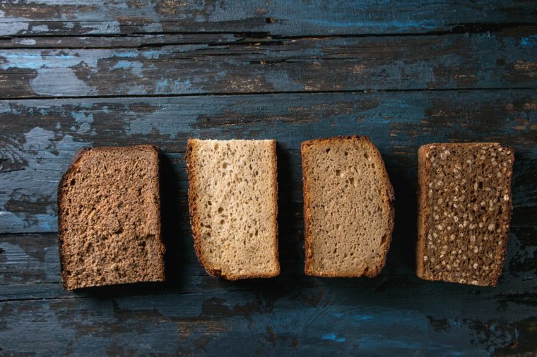 Variety loaves of sliced homemade rye bread whole grain and seeds over old dark wooden background. Top view, space. Healthy eating