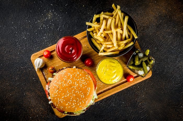 Various party food, Hamburgers, French fries, potato chips, pickled cucumbers, onions, tomatoes and cold beer bottles, rusty black concrete background copy space