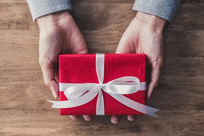 Woman hands in gray sweater on wood table giving red Christmas gift box wrapped with white ribbon - top view with copy space