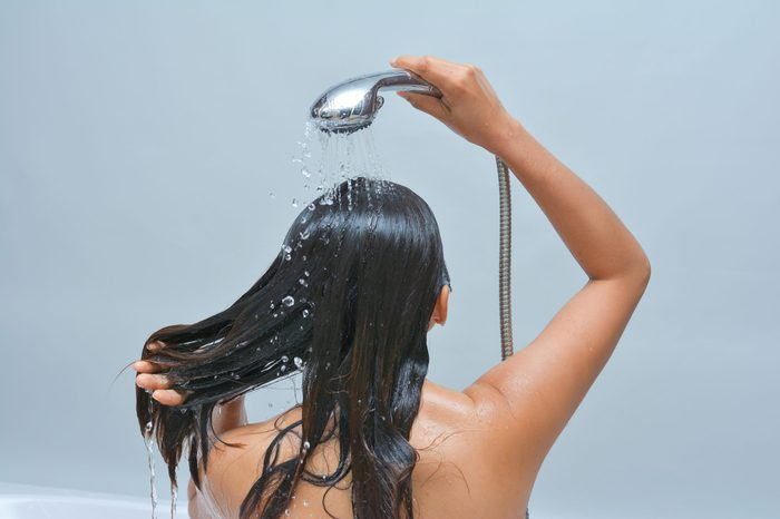 Woman washing her hair with shower, water