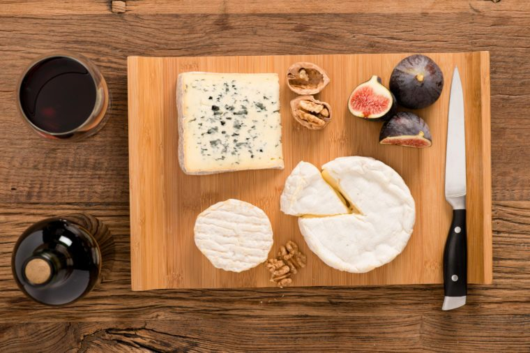 above overhead view flat lay assortment of various cheese with traditional bread fruits glass and bottle of red wine on old wooden table