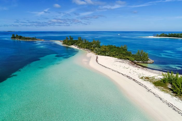 Aerial view of Munjack Cay with bay and beach in Abaco, Bahamas. Green turtles and stingrays inhabit the area.