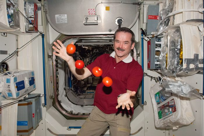 Engineer Chris Hadfield with floating tomatoes