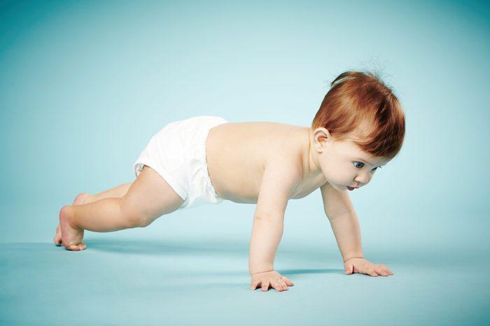 sweet child crawls on blue background