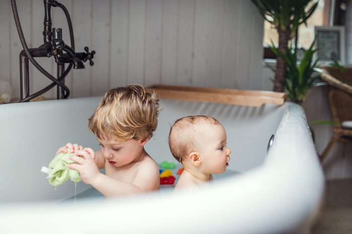 Two toddler children having a bath in the bathroom at home.